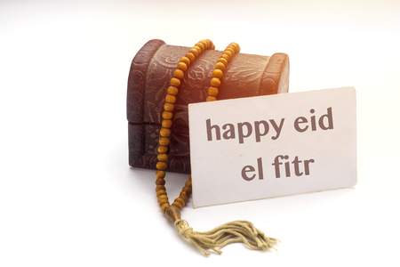 happy eid el fitr text on white card and brown rosary muslim with small wooden box