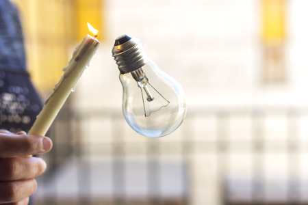 woman hold a candle for illuminate a bulb Stock Photo