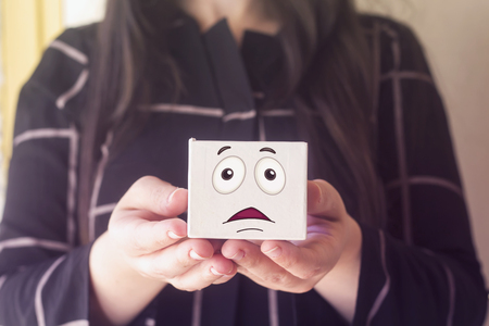 woman with beautiful hair holding white box with scared  face emoticon