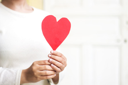 woman hand holding red paper heart shape for valentine's day