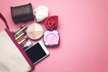 makeup bag contain a differents colorful lipsticks and face powder and phone, jewelry box with red and white flowers  on pink background Stock Photo