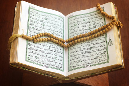 rosary and holy quran book on wood stand Stok Fotoğraf