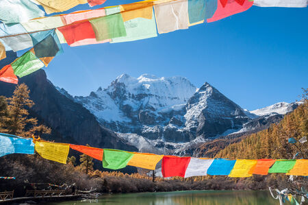 Pearl Lake with prayer flag and mt. Chenrezig   in Yading national level reserve, Daocheng, Sichuan Province, China.