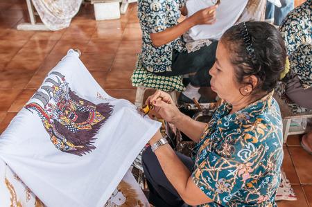 batik: Bali, Indonésie, Avril 21,2010: femme balinaise applique la cire sur un morceau de batik à Bali, Indonesia.Batik de décisions est une partie importante de la culture indonésienne.