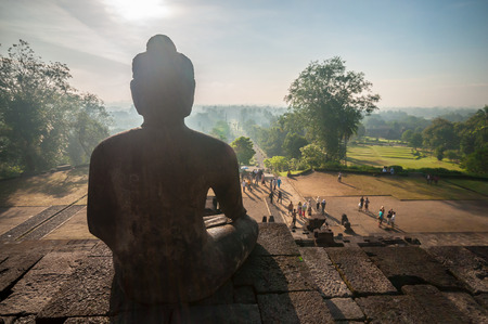 stone buddha: Yogyakarta,Indonesia - April 27,2010 : Tourist visiting   Borobudur Temple at morning  in Yogyakarta Java Indonesia. Borobudur Temple is one of the most visited temple in Indonesia.