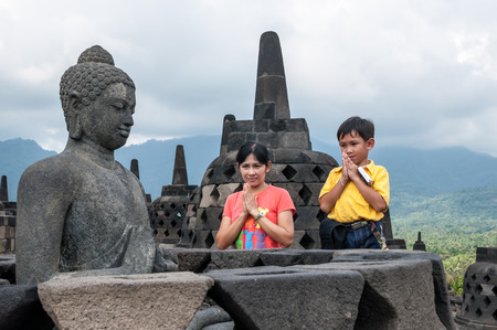 Yogyakarta,Indonesia - April 27,2010 : Tourists praying at  Borobudur Temple at morning  in Yogyakarta Java Indonesia. Borobudur Temple is one of the most visited temple in Indonesia.