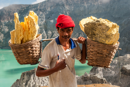 Kawah Ijen, Indonesia - April 24,2010 :  Worker carries sulfur inside Ijen crater  in Ijen Volcano, Indonesia. He carries the load of around 60kg to the top of the rip and then 3km down.