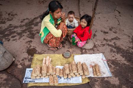 log basket: Mandalay, Myanmar - March 16,2011 : The Myanmar vendoe selling Tanaka wood  , A traditional burmese yellowish cosmetic paste made from the thanaka tree, at morning street market in Mandalay city.The biggest local market of the city in Mandalay, Myanmar.