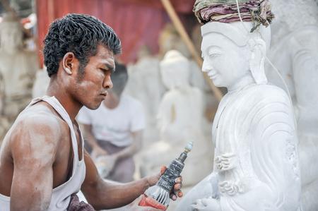 trinchante: Mandalay Myanmar marzo de 152011: Un tallador utilizando una herramienta en un mármol para tallar una estatua de Buda en Mandalay de Myanmar.