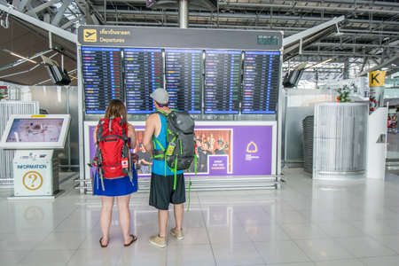 departures board: Bangkok,Thailand-August 31,2014 : An unidentified passengers looks at the departures board at Suvarnabhumi International Airport in Bangkok ,Thailand.This airport is handling about 45 million passengers annually. Editorial