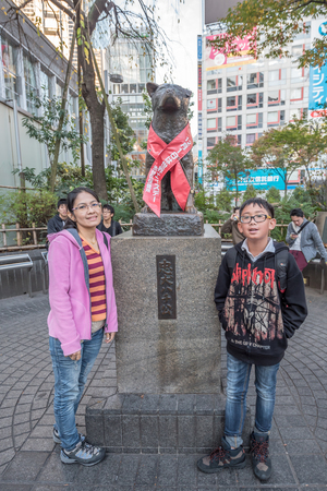remembered: Tokyo, Japan - November 20, 2015: Unidentified people at Bronze statue of Hachiko at Shibuya Station. A dog is remembered for his remarkable loyalty to his owner which continued for many years, Tokyo, Japan.