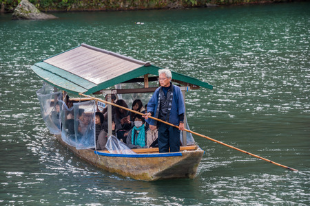 Kyoto, Japan - November 26,2015 :  Unidentified people sail boates in the Oi river for tourist who travel to Arashiyama mountain area in Kyoto ,Japan.
