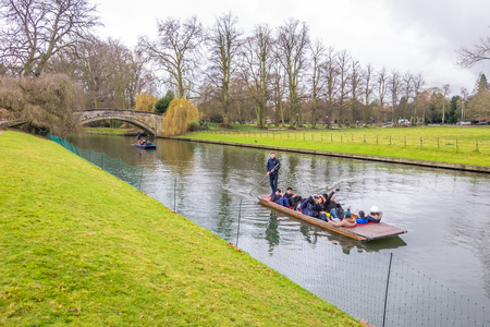 Oxford, UK - December 21, 2016 : Unidentified people in a boat over the river Cherwell near university of Oxford botanic gardens , Oxford, United Kingdom.