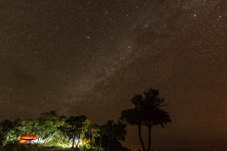 Camping fire under the amazing starry sky with a lot of shining stars in Thailand