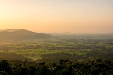 Beautiful scenery during sunrise time with mountain and savannah field in Thailand