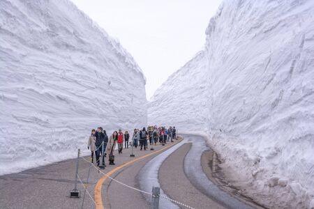 Tateyama, Japan - April 21, 2019 : Unidentified tourists visiting snow corridor on Tateyama Kurobe Alpine Route, Japanese Alp in Tateyama, Japan. Zdjęcie Seryjne - 135906793