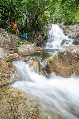 Phatthalung, Thailand-December  28, 2019: The trekkers trekking in green forest river stream in jungle of Phatthalung, Thailand. Publikacyjne