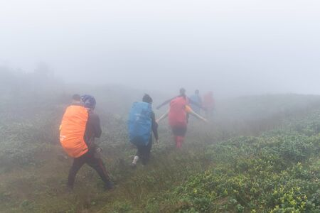 Phatthalung, Thailand-December  31, 2019: The trekkers trekking on foggy the mountains in jungle of Phatthalung, Thailand.