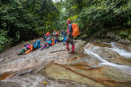 Phatthalung, Thailand-December  29, 2019: The trekkers trekking in green forest river stream in jungle of Phatthalung, Thailand.