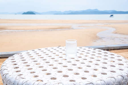 A glass of drinking water on white table next to the beach restaurant