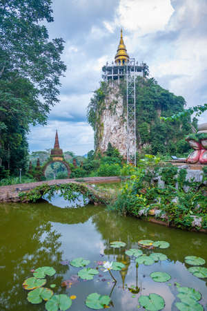 View of the temple gate and golden pagoda at Khao Na Nai Luang Dharma Park in Surat Thani province of Thailand.