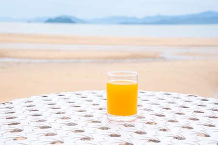 A glass of orange juice on white table next to the beach restaurant Zdjęcie Seryjne