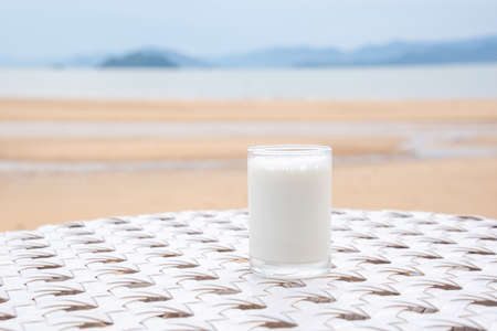 A glass of milk on white table next to the beach restaurant