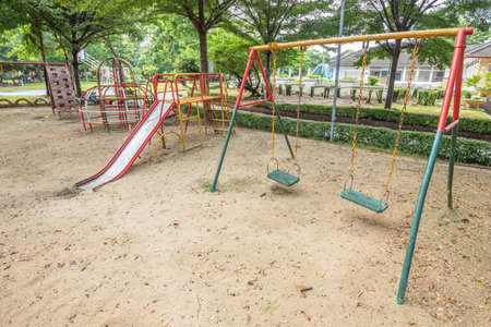 Old empty playground with metal structures at the garden park in Thailand