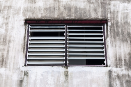 window coverings: Moulder window louver with old building Stock Photo