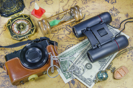 travel picture set with pocket camera binocular compass hourglass money on old world map Imagens