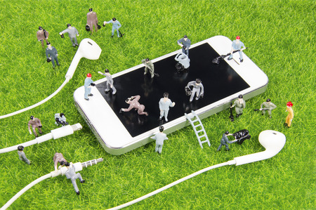 mini toy worker working on a smartphone on a grass