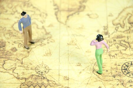 figuring: mini model of a man woman on a old world map