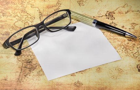 carta e penna: paper,pen and eyeglasses on a old world map Archivio Fotografico