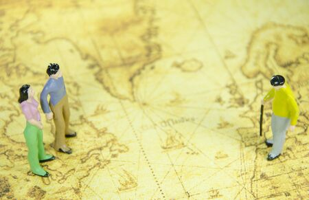figuring: mini model of a man woman and oldman on a old world map
