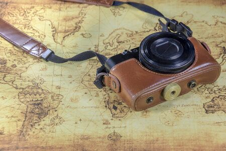 compact camera: dirty pocket compact camera on a old world map Stock Photo