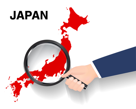 Hand use magnifying glass searching on Japan map