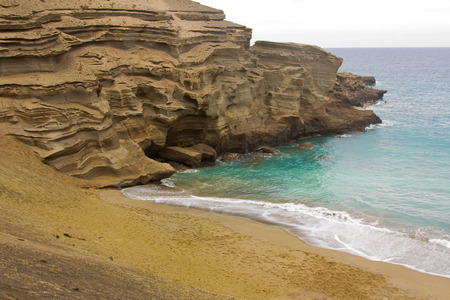 big island: Green Sand Beach (Papakolea Beach) sand is almost exclusively composed of olivine grains which are very unusual in most beach sands. Sand comes from an eroded tuff cone that contains lots of olivine. Stock Photo