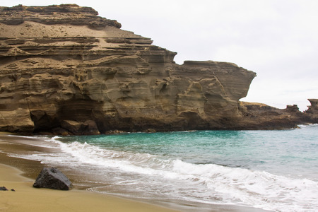 exclusively: Green Sand Beach (Papakolea Beach) sand is almost exclusively composed of olivine grains which are very unusual in most beach sands. Sand comes from an eroded tuff cone that contains lots of olivine. Stock Photo
