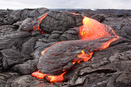 Lava loses heat rapidly and its surface turns black and is pushed into wrinkles by moving interior. Kilauea volcano, Puu Oo vent.