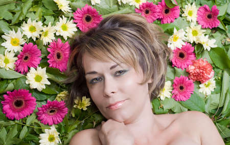 Woman lying on a bed of flowers