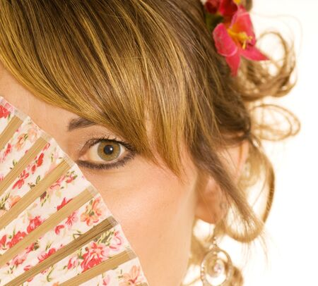 close up of womans face partly hidden by a fan Stock Photo