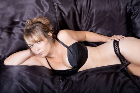 Woman on black sheets in black lingerie