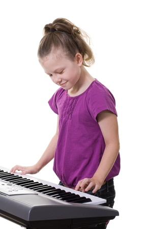 young girl playing music on a keyboard