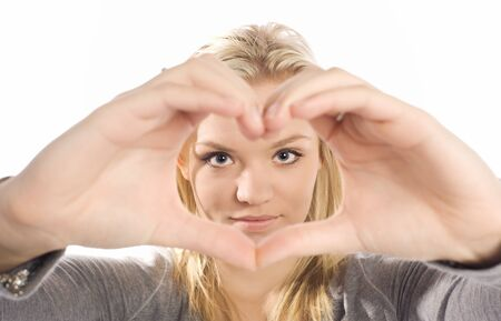 beautiful young woman framing her face with hands in heart shape