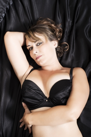 attractive woman in lingerie lying on black satin sheets Stock Photo