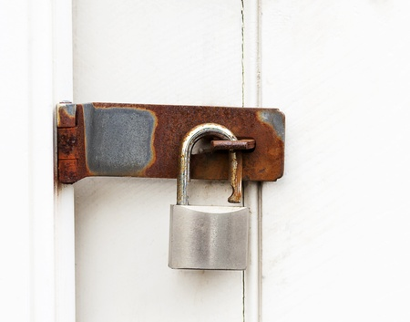 hasp: close up of a rusty padlock on a wooden door Stock Photo