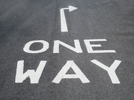 one way sign on tarmac road with arrow pointing right Stock Photo