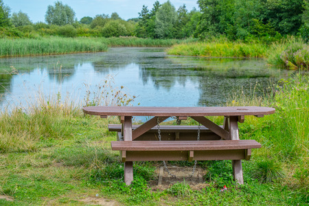 picnic bench in a rural setting next to a lake in summer Stock Photo