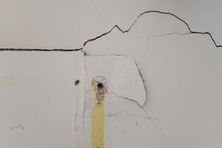 plasterboard: badly damaged interior plasterboard wall with drill holes Stock Photo