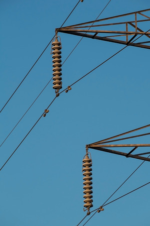 electricity pylon insulators and arms against a blue sky Stock Photo
